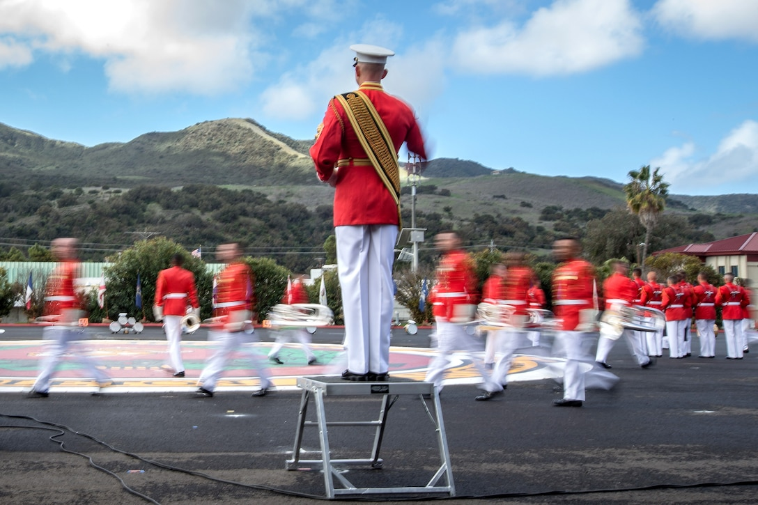 Marines wearing red move in front of mountains.