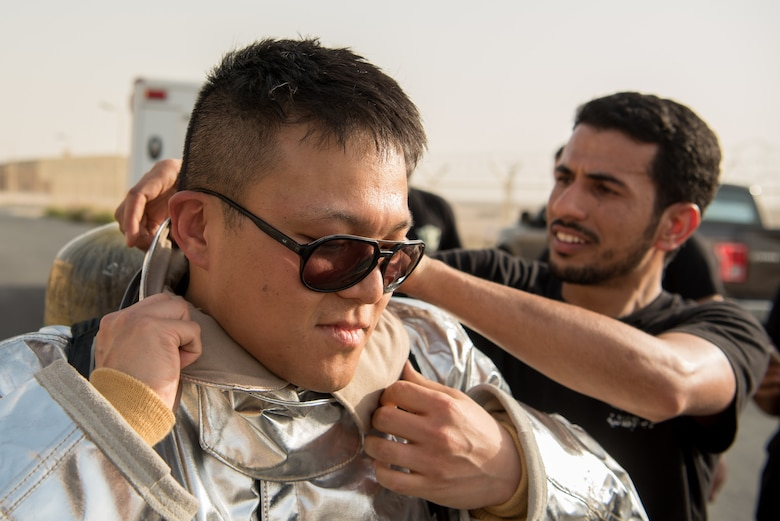 2nd Lt. Taegyung Lee (left), project manager from the 379th Expeditionary Civil Engineer Squadron, is assisted by a firefighter from the Qatar Emiri Air Force as Lee prepares to participate in a firefighter challenge exercise at Al Udeid Air Base, Qatar, March 8, 2018. The a exercise, a strenuous course designed to test physical fitness and fire response capabilities, was organized by firefighters from the 379th ECES and QEAF. (U.S. Air Force photo by Staff Sgt. Joshua Horton)