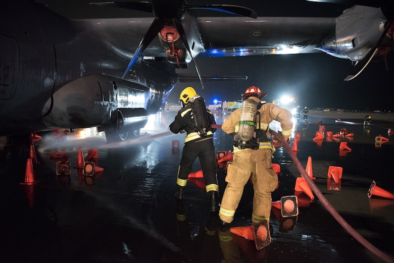 Firefighters from the 379th Expeditionary Civil Engineer Squadron and Qatar Emiri Air Force collaborate in a joint training exercise at Al Udeid Air Base, Qatar, Feb. 28, 2018. The exercise, a simulated response to a C-130 Hercules aircraft fire emergency, marks the first instance of the partner forces responding together in the same vehicles. (U.S. Air Force photo by Staff Sgt. Joshua Horton)