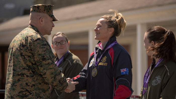Australian athlete Maj. Kelliegh Jackson shakes hands with U.S. Marine Corps Sgt. Maj. Karl Simburger during the 2018 Marine Corps Trials cycling competition medal ceremony at Marine Corps Base Camp Lejeune, N.C., March 18, 2018. The Marine Corps Trials promotes recovery and rehabilitation through adaptive sport participation and develops camaraderie among recovering service members and veterans. It is an opportunity for RSMs to demonstrate their achievements and serves as the primary venue to select Marine Corps participants for the DoD Warrior Games.