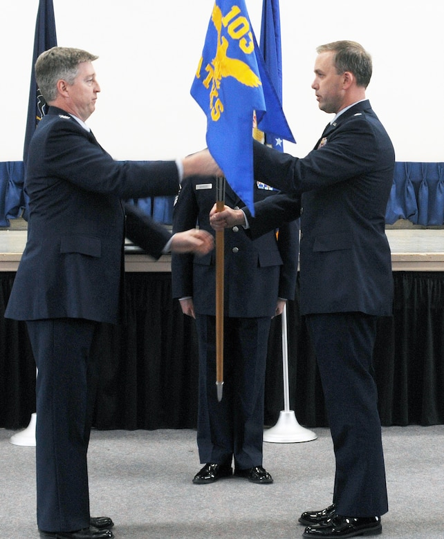 Col. John O'Brien, 111th Attack Wing Operations Group commander, hands off the guidon to Lt. Col. Peter as he assumes command of the 103rd Attack Squadron, Horsham Air Guard Station, Pa. March 10, 2018. Peter stated he intends to continue forward on the current mission path, while extending on the great work of his predecessor.
