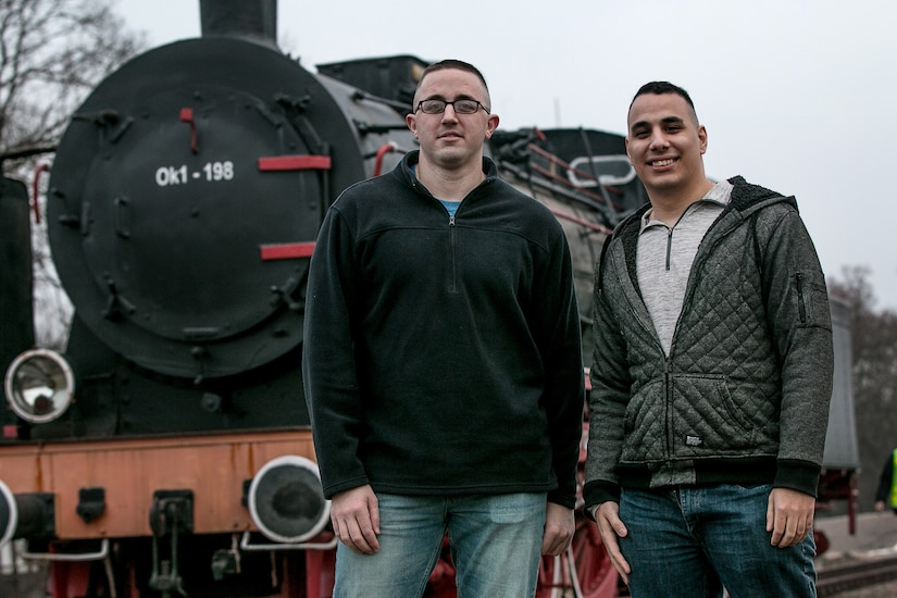 Two airmen pose for a photo in front of a train in Poland.