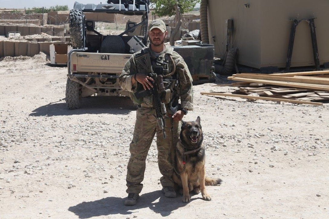 U.S. Air Force Staff Sgt. David Mussio, 20th Security Forces Squadron (SFS) military working dog (MWD) trainer, stands with MWD Marky in a deployed location, circa 2015.