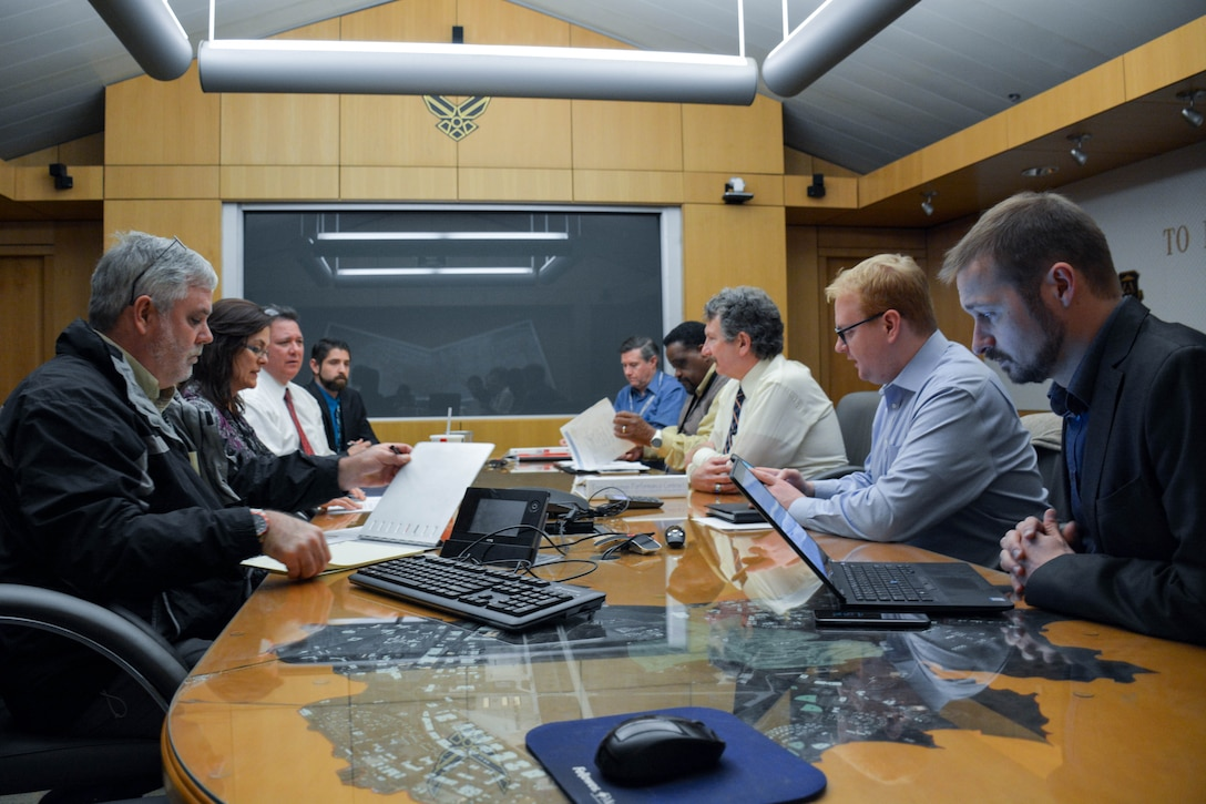 low-angle photo of nine people surrounding a table