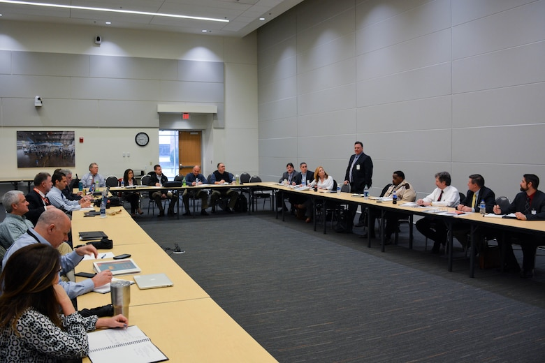 Approximately 20 people surround a u-shaped table. A man is standing and presenting to the group.