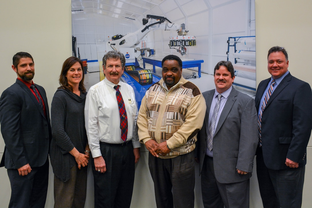 Six individuals pose in front of photo at NASA Langley Research Center