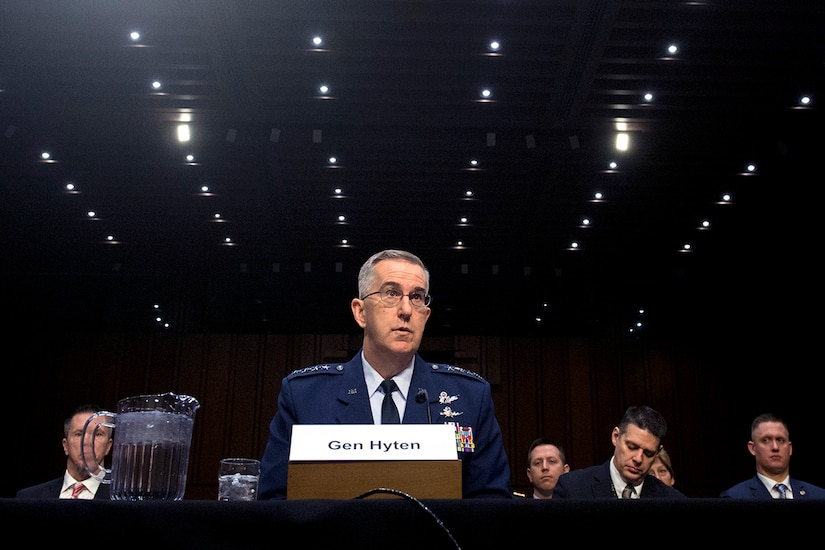 An Air Force general sits behind a table with rows of lights behind him.