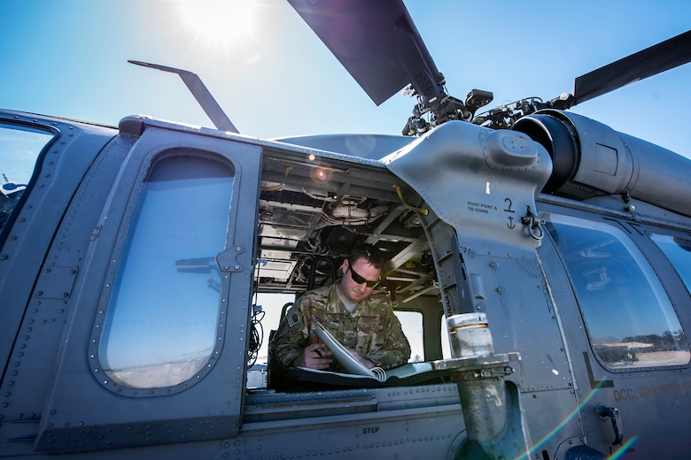 Tech. Sgt. Joshua Poe, 41st Rescue Squadron (RQS) special missions aviator, reads a flight plan, March 15, 2018, at Moody Air Force Base, Ga. Airmen from the 41st RQS and 723d Aircraft Maintenance Squadron conducted pre-flight checks to ensure that an HH-60G Pave Hawk was fully prepared for a simulated combat search and rescue mission. (U.S. Air Force photo by Airman Eugene Oliver)