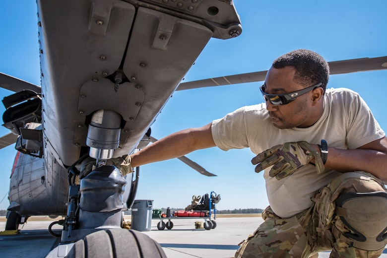 Senior Airman Latrell Solomon, 41st Rescue Squadron (RQS) special missions aviator, inspects the landing gear of an HH-60G Pave Hawk, March 15, 2018, at Moody Air Force Base, Ga.  Airmen from the 41st RQS and 723d Aircraft Maintenance Squadron conducted pre-flight checks to ensure that an HH-60G Pave Hawk was fully prepared for a simulated combat search and rescue mission.  (U.S. Air Force photo by Airman Eugene Oliver)