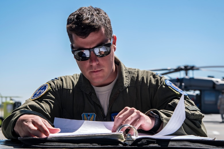 A pilot from the 41st Rescue Squadron (RQS) reads a flight plan, March 15, 2018, at Moody Air Force Base, Ga. Airmen from the 41st RQS and 723d Aircraft Maintenance Squadron conducted pre-flight checks to ensure that an HH-60G Pave Hawk was fully prepared for a simulated combat search and rescue mission. (U.S. Air Force photo by Airman Eugene Oliver)