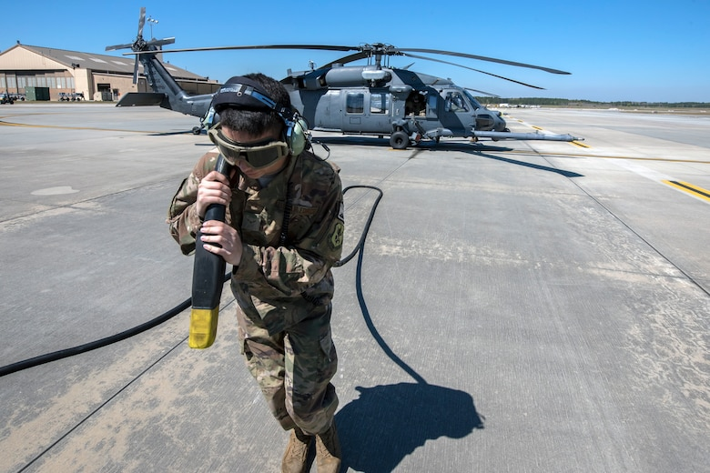 Airman First Class Ryan Lenig, 723d Aircraft Maintenance Squadron (AMXS) crew chief, pulls a power cable away from an HH-60G Pave Hawk, March 15, 2018, at Moody Air Force Base, Ga. Airmen from the 41st Rescue Squadron and the 723d AMXS conducted pre-flight checks to ensure that an HH-60G Pave Hawk was fully prepared for a simulated combat search and rescue mission. (U.S. Air Force photo by Airman Eugene Oliver)