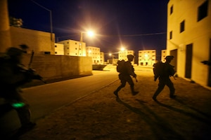 Marines run to cover during a night exercise under lights.