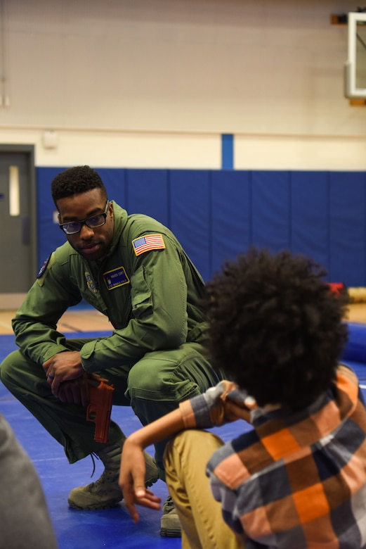 Staff Sgt. Ronald Cole, 436th Security Forces Squadron Raven, answers a Central Middle School student's question during a demonstration by the Ravens March 8, 2018, in Dover, Del. The Ravens gave the kids a glimpse of the training they go through to become Ravens, including baton techniques and how to unarm an enemy. (U.S. Air Force Photo by Airman 1st Class Zoe M. Wockenfuss)