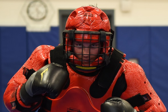 """Staff Sgt. Michael Rice, 436th Security Forces Squadron Raven, wears the """"Red Man"""" suit during a demonstration March 8, 2018, at Central Middle School in Dover, Del. Rice served as the aggressor in the sparing sessions while his opponents used batons to defend themselves.  (U.S. Air Force Photo by Airman 1st Class Zoe M. Wockenfuss)"""
