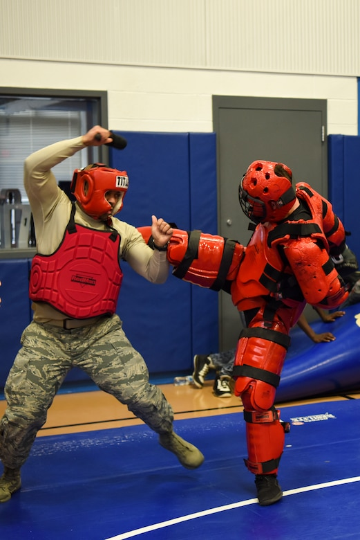Master Sgt. Jamie Beard, 436th Maintenance Squadron first sergeant, and Staff Sgt. Michael Rice, 436th Security Forces Squadron Raven, demonstrate baton training at March 8, 2018, at Central Middle School in Dover, Del. Beard and Rice showed the students some of the baton tactics they use during their Raven training. (U.S. Air Force Photo by Airman 1st Class Zoe M. Wockenfuss)
