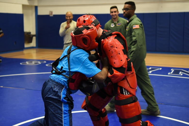 "Staff Sgt. Michael Rice, 436th Security Forces Squadron raven, and a Central Middle School student partake in baton training during a demonstration by the Ravens March 8, 2018, at Central Middle School in Dover, Del. The students were given an opportunity to go against the ""Red Man"" after being shown some of the baton strikes the Ravens use. (U.S. Air Force Photo by Airman 1st Class Zoe M. Wockenfuss)"