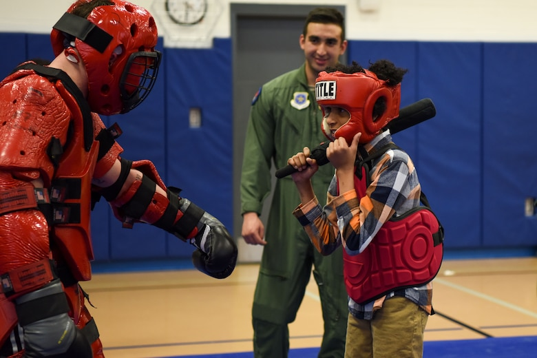 "Staff Sgt. Michael Rice, 436th Security Forces Squadron Raven, and a Central Middle School student partake in baton training during a demonstration by the Ravens March 8, 2018, at Central Middle School in Dover, Del. The students were given an opportunity to try the skills they were shown during the demonstration by defending themselves from a ""Red Man"" aggressor. (U.S. Air Force Photo by Airman 1st Class Zoe M. Wockenfuss)"
