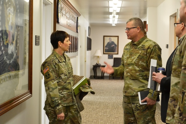 Army Maj. Gen. Barbara Holcomb, U.S. Army Medical Research and Material Command commanding general, left, speaks with Brig. Gen. Mark Simerly, DLA Troop Support commander, right, at DLA Troop Support, March 16, 2018, in Philadelphia.