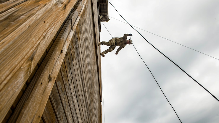 A sailor rappels from a tall building using a rope technique.