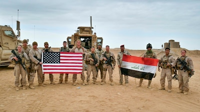 U.S. Marines and Iraqi security forces pose holding their nations' flags.