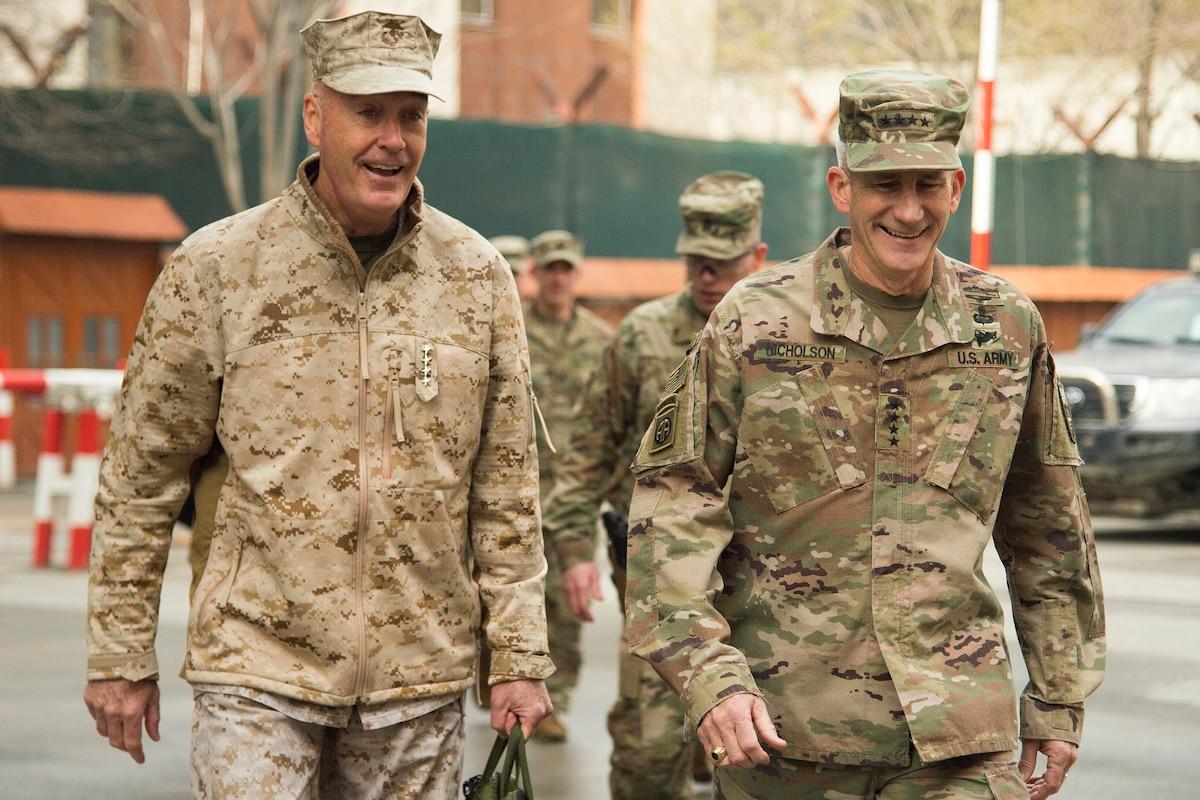 Two U.S. military leaders walk together in Afghanistan.