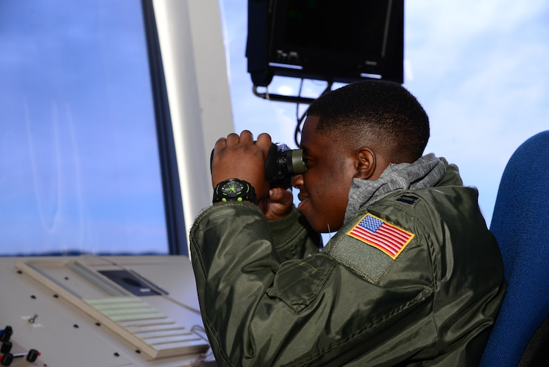 "Kareem Bennett ""glasses"" the horizon March 16, 2018, from the 436th Operations Support Squadron air traffic control tower on Dover Air Force Base, Del. Bennett spent the day touring the installation with members of the 3rd Airlift Squadron as an honorary pilot for the day. (U.S. Air Force photo by Staff Sgt. Aaron J. Jenne)"