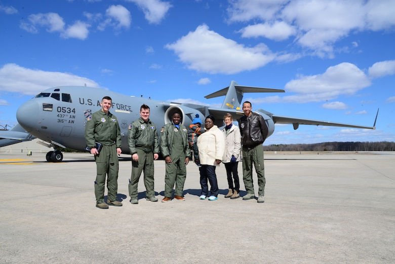 Members of the 3rd Airlift Squadron stand in front of a C-17 Globemaster III with Kareem Bennett (center) and his family March 16, 2018, at Dover Air Force Base, Del. Bennett was the second participant in the 3rd AS Pilot for a Day program. (U.S. Air Force photo by Staff Sgt. Aaron J. Jenne)