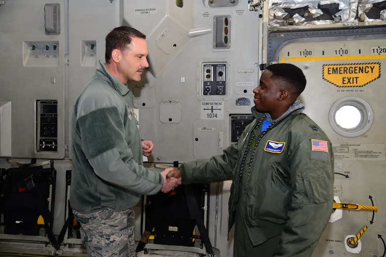 Col. Ethan Griffin, 436th Airlift Wing commander, presents a coin to Kareem Bennett during the 3rd Airlift Squadron Pilot for a Day event March 16, 2018, at Dover Air Force Base, Del. Bennett visited multiple base shops during his tour, including the 436th Operations Support Squadron's aircrew flight equipment shop, the air traffic control tower, radar approach control, the 436th Security Forces Squadron's combat arms training facilities and the military working dog kennels. (U.S. Air Force photo by Staff Sgt. Aaron J. Jenne)