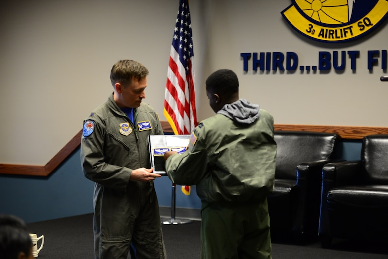 Lt. Col. Mark Radio, 3rd Airlift Squadron commander, holds the Pilot for a Day plaque while Kareem Bennett affixes his nametape to it during a squadron roll call March 16, 2018, at Dover Air Force Base, Del. Flying squadrons traditionally hold a ceremony for outgoing or retiring members that involves placing their nametape on a board to commemorate their service to the organization. (U.S. Air Force photo by Staff Sgt. Aaron J. Jenne)