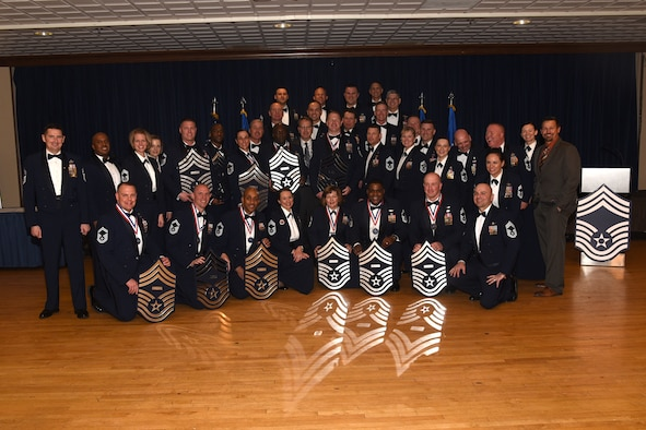 Newly promoted, current, and retired chief master sergeants gather in front of the stage after 11 Airmen were promoted to chief at The Club on Peterson Air Force Base, Colo., March 16, 2018. Becoming a chief is an obligation of the highest importance. It encompasses honor, integrity, dedication and trust. (U.S. Air Force photo by Robb Lingley)