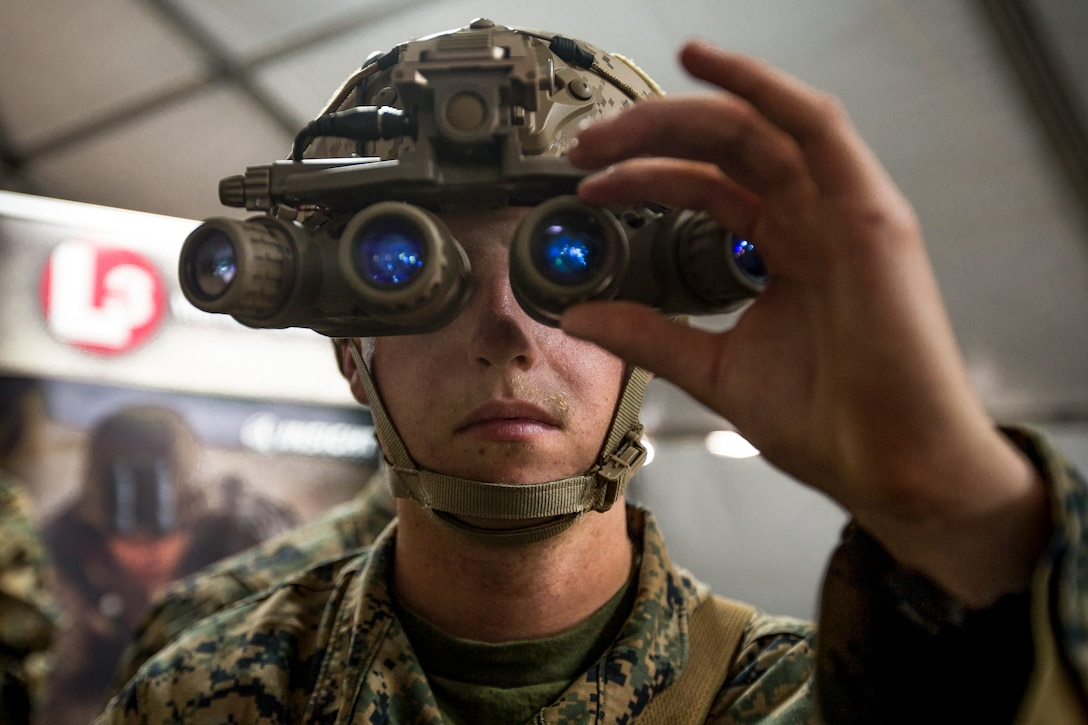 A Marine looks through an optical device with four blue lenses.