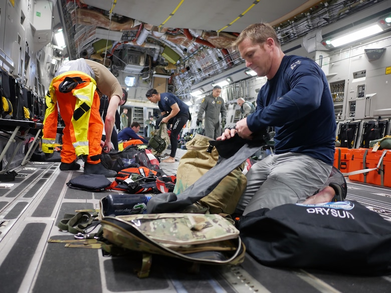 Tech. Sgt. Westley Loignon, 103rd Rescue Squadron pararescueman and jumpmaster, prepares his life support equipment aboard a C-17 Globmaster III from the 204th Airlift Squadron March 4, 2017, at Joint Base Pearl Harbor-Hickam, Hawaii.