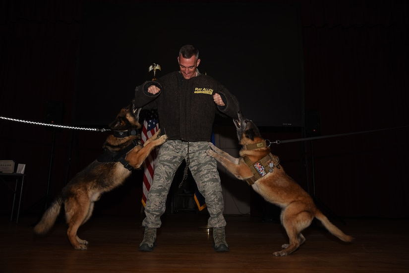 Marky, left, and Astra, 20th Security Forces Squadron military working dogs, perform their final bite during their retirement ceremony as Col. Daniel Lasica, 20th Fighter Wing commander, stands in a bite suit at Shaw Air Force Base, S.C., March 14, 2018.
