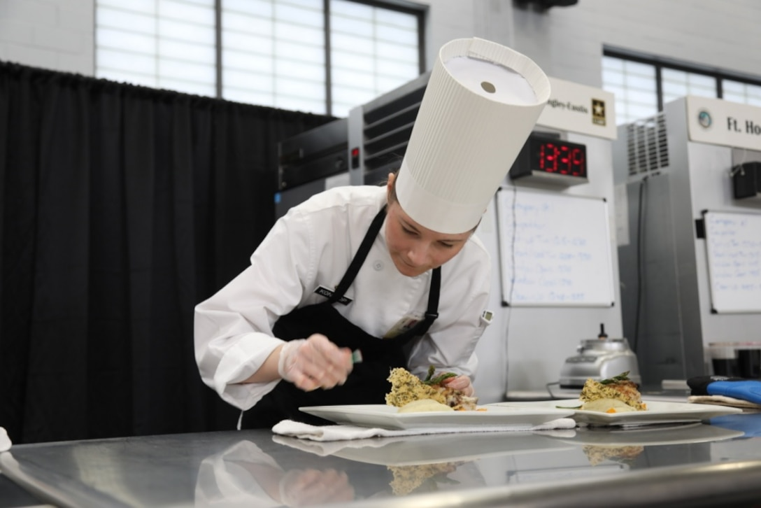 An Army chef plates a chicken dish.