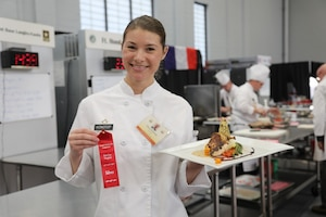 An Army chef holds a second-place ribbon and her winning dish.