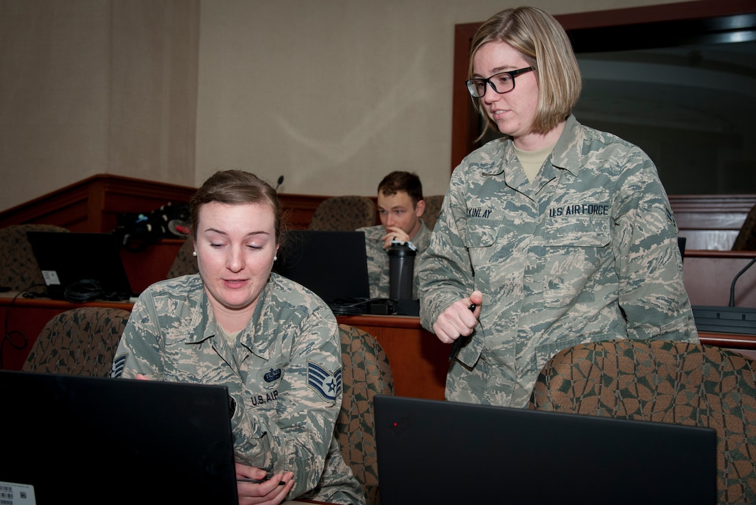 Staff Sgt. Amanda Morgan, Cybersecurity Foundry Course student, receives assistance from Airman 1st Class Shelby McKinlay, a CFC instructor, at MacDill Air Force Base, Fla., March 9, 2018. Course instructors taught 100 cyberspace students various cybersecurity functions, processes, procedures and data analysis skills to further their ability to secure the Air Force Network. (U.S. Air Force photo by Senior Airman Mariette Adams)