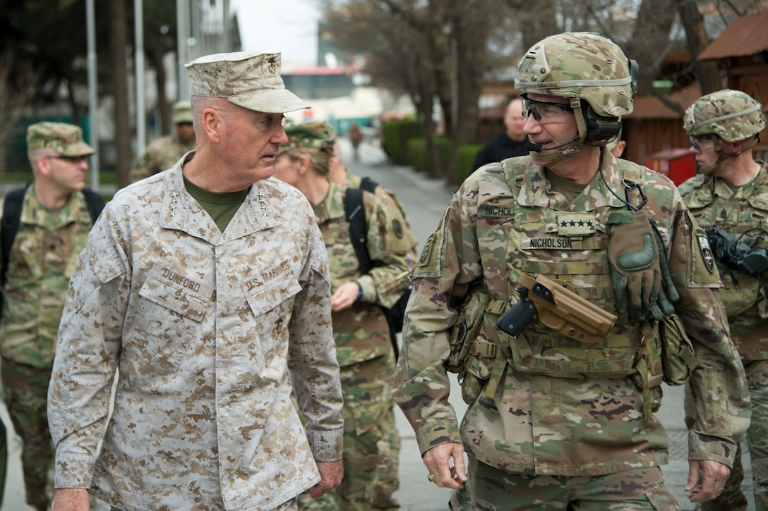 Two U.S. military leaders converse as they walk down a street in Afghanistan.