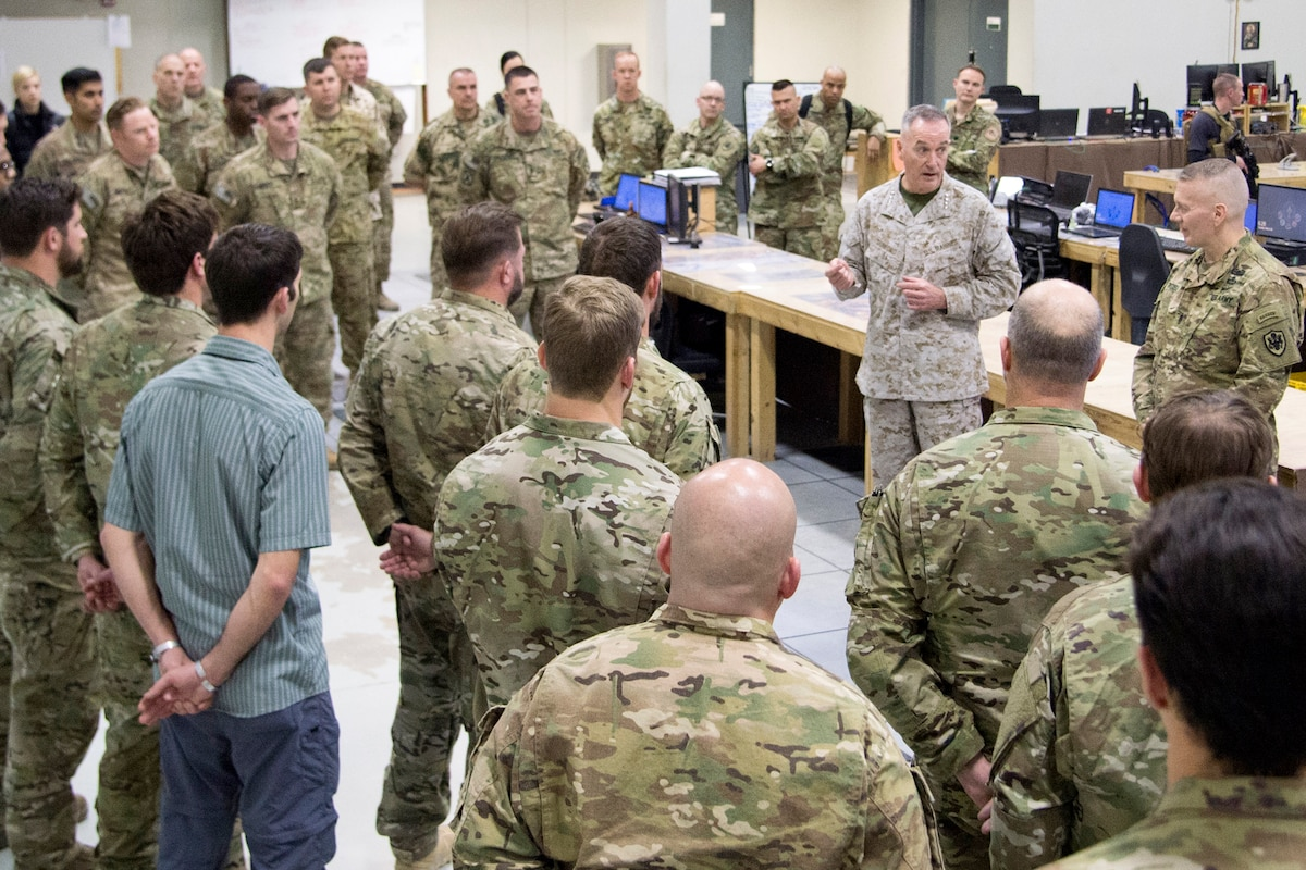 The chairman of the Joint Chiefs of Staff talks to service members standing around him.