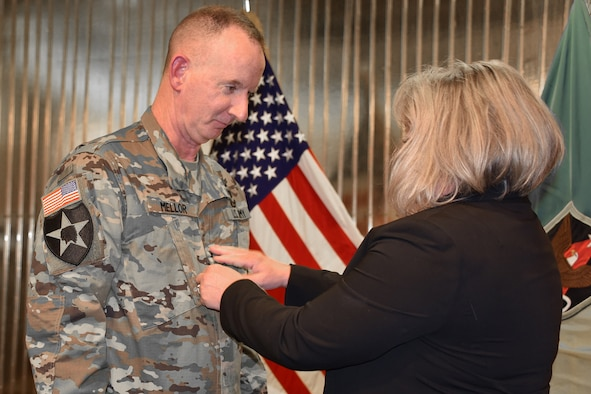 Col. Glenn O. Mellor, commander, 53rd Signal Battalion, 1st Space Brigade, U.S. Army Space and Missile Defense Command/Army Forces Strategic Command, receives his new rank from his wife Cyndi during a promotion ceremony March 15 at The Club on Peterson Air Force Base, Colo. (U.S. Air Force photo by Dottie White)