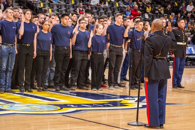 Capt. Anthony Rollins, Officer Selection Officer with Recruiting Station Denver, administers the Oath of Enlistment to future Marines from the local area on the Nuggets basketball court inside the Denver Pepsi Center, Feb.1, 2018. Family, friends and local Marines also watched the event, that included more than 80 future Marines with RS Denver.