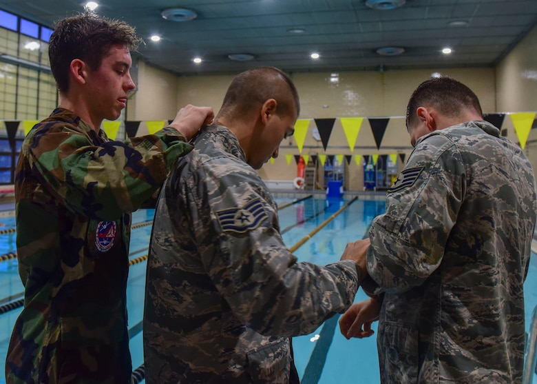 (From Left) U.S. Civil Air Patrol Cadet 1st Lt. Thomas Hall, U.S. Air Force Staff Sgt. Michael Svoleantopoulos, 497th Operation Support Squadron weapons tactician, and U.S. Air Force Staff Sgt. Dajon Begin, 45th Intelligence Squadron full motion video imagery mission supervisor, help each other prepare their uniforms for the pool at Fort Eustis' Anderson Field House at Joint Base Langley-Eustis, Virginia, March 6, 2018.