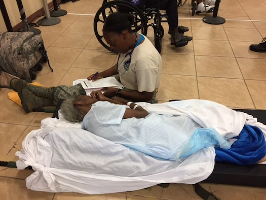 Maj. Kisha Wood, a medic with the 375th Medical Group based at Scott Air Force Base, assists an elderly patient after Hurricane Maria at Henry E. Rohlsen Airport, near Christiansted, St. Croix, U.S. Virgin Islands Sept. 24, 2017. Wood was part of a U.S. Air Force En Route Patient Staging System team that deployed to St. Croix to help evacuate patients off the island. The team created an aeromedical evacuation staging area for patients to evacuate, fostering a safe environment. (Photo by Lt. Col. Elizabeth Anderson-Doze)