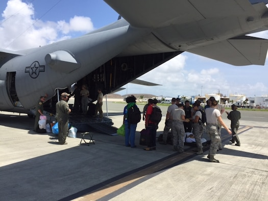 Members of a U.S. Air Force En Route Patient Staging System team from the 375th Medical Group based at Scott Air Force Base at Henry E. Rohlsen Airport, near Christiansted in St. Croix, U.S. Virgin Islands load the first patients onto an Air Force C-17 Globemaster III, Sept. 23, 2017. The team deployed to St. Croix to provide aeromedical evacuation support following Hurricane Maria. Patients began arriving at the airport less than an hour after the team arrived. (Photo by Lt. Col. Elizabeth Anderson-Doze)