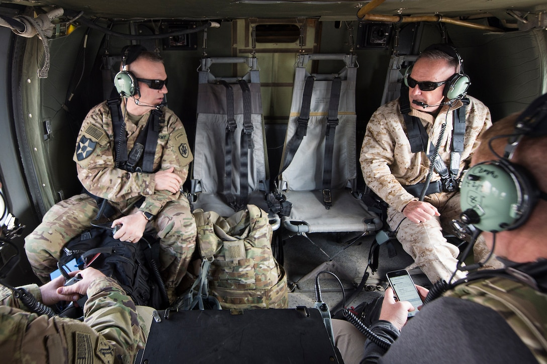 Joint Chiefs chairman and his senior enlisted advisor talk aboard a helicopter flying over Afghanistan.