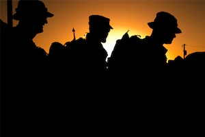 A silhouette of three service members.
