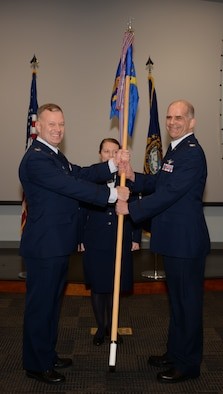 Col. John W. Pogorek passes a guidon to Col. John Mirabello on March 11, 2018, at Pease Air National Guard Base, N.H. Mirabello, the New Hampshire state air surgeon, assumed command of the 157th Medical Group. (N.H. Air National Guard photo by Senior Airman Ashlyn J. Correia)