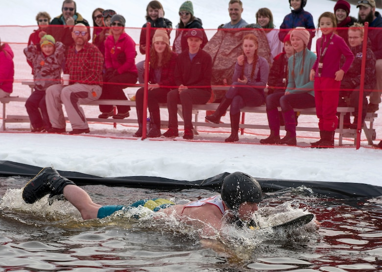 Ross Funches, a participant of the 2018 Slush Cup, swims to the finish line at Joint Base Elmendorf-Richardson's Hillberg Ski Area, March 18, 2018.The Slush Cup is a two-fold annual event celebrating the change in weather, consisting of skiers and snowboarders trying to make it across a man-made slush pond without falling.