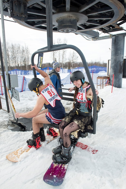Pedro Pena and Courtney Duran, participants of the 2018 Slush Cup, sit on a ski lift at Joint Base Elmendorf-Richardson's Hillberg Ski Area, March 18, 2018. The Slush Cup is a two-fold annual event celebrating the change in weather, consisting of skiers and snowboarders trying to make it across a man-made slush pond without falling.