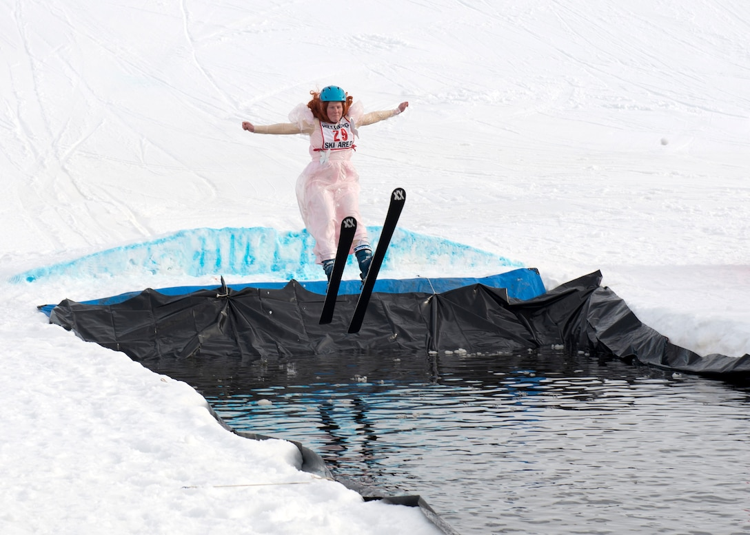 Laura Long, a participant of the 2018 Slush Cup, skis into the slush pond at Joint Base Elmendorf-Richardson's Hillberg Ski Area, March 18, 2018. The Slush Cup is a two-fold annual event celebrating the change in weather, consisting of skiers and snowboarders trying to make it across a man-made slush pond without falling.