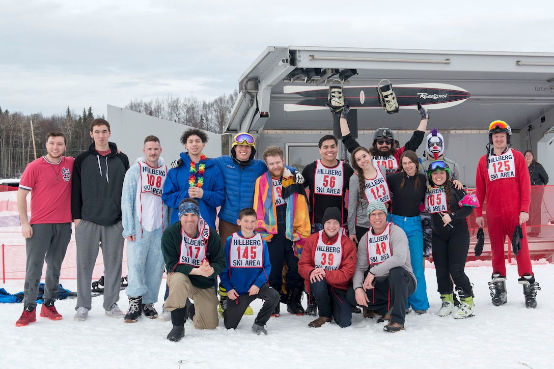 The 2018 Slush Cup participants stand as a group at the Joint Base Elmendorf-Richardson Hillberg Ski Area, March 18, 2018. The Slush Cup is a two-fold annual event celebrating the change in weather, consisting of skiers and snowboarders trying to make it across a man-made slush pond without falling.
